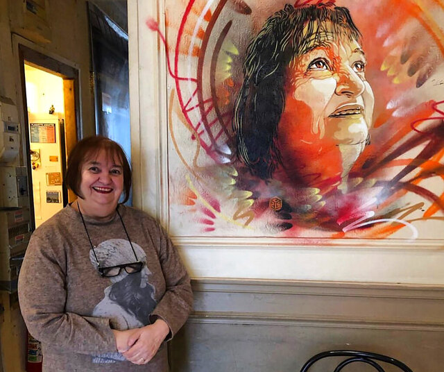 In this undated photo provided by Christian Guemy, Viviane Bouculat poses by a portrait of her by street artist Christian Guemy, known as C215, late in 2019, and painted directly on the wall of restaurant l'Annexe, in the Paris suburb of Ivry-sur-Seine. For three decades, Viviane Bouculat was the owner, cook and beating heart of l'Annexe. Anyone was welcome, but over the years it became a haven for local artists, actors and musicians. Bouculat died March 31, 2020 of coronavirus. She was 65. (Christian Guemy via AP)