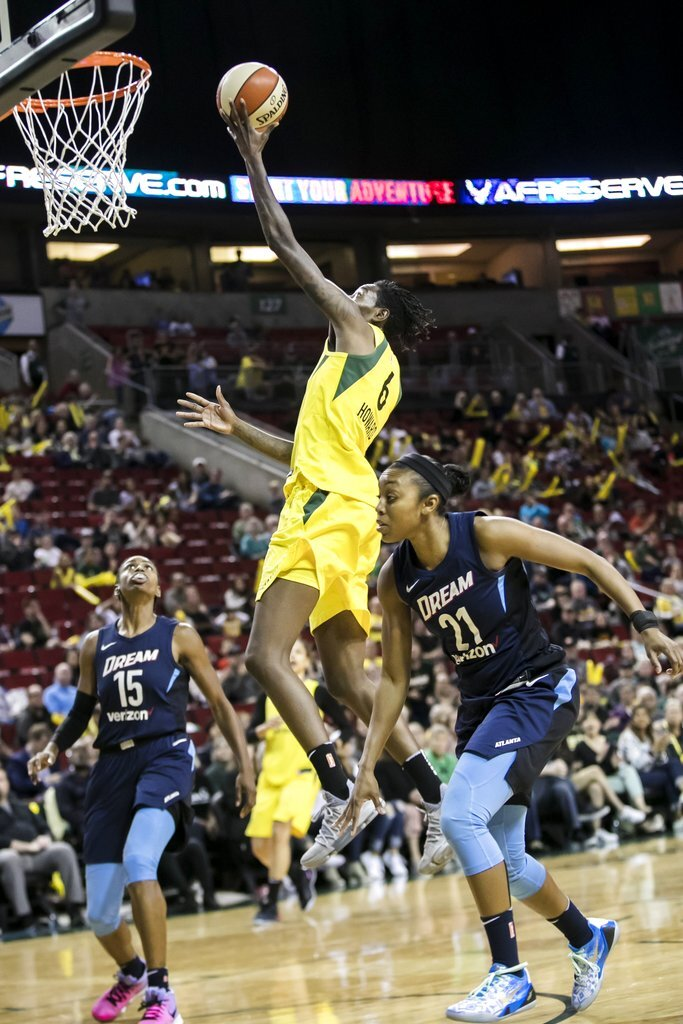 FILE - In this June 10, 2018, file photo, Seattle Storm forward Natasha Howard puts in a layup over Atlanta Dream guards Tiffany Hayes and Renee Montgomery, right, during the second half of a WNBA basketball game in Seattle. Almost every WNBA team this season will go through a hellacious road trip because of the FIBA World Cup in September that is compacting the season.  Atlanta is in the midst of its difficult stretch, playing in six different cities across the country in the past week and a half. (Bettina Hansen/The Seattle Times via AP, File)