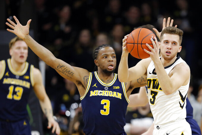 Iowa guard Jordan Bohannon grabs a loose ball in front of Michigan guard Zavier Simpson (3) during the first half of an NCAA college basketball game Friday, Feb. 1, 2019, in Iowa City, Iowa. (AP Photo/Charlie Neibergall)