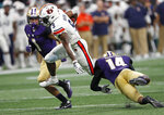 Auburn Tigers running back Kam Martin (9) tries to get past Washington's JoJo McIntosh (14) and Byron Murphy (1) in the first half of an NCAA college football game Saturday, Sept. 1, 2018, in Atlanta. (AP Photo/John Bazemore)