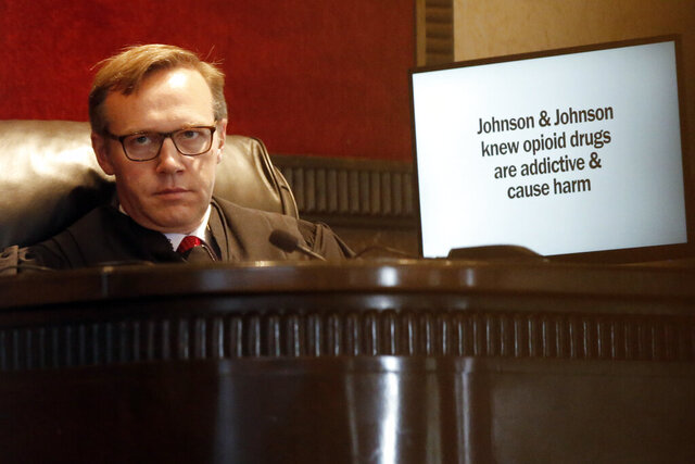FILE - In this May 28, 2019, file photo, Judge Thad Balkman listens in Norman, Okla., during opening arguments as a slide from the state's presentation is displayed on a monitor in Oklahoma's trial against drugmakers blamed for contributing to the opioid crisis.  Judge Balkman reduces amount Johnson & Johnson must pay state to help clean up opioid crisis by $107 million to $465 million on Friday Nov. 15, 2019.  (AP Photo/Sue Ogrocki, File)
