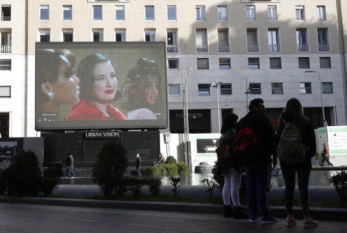A giant screen streams a Moschino fashion live show presenting the women's Fall Winter 2021-22 collection, unveiled during the Fashion Week in Milan, Italy, Thursday, Feb. 25, 2021. (AP Photo/Antonio Calanni)