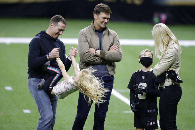 New Orleans Saints quarterback Drew Brees, left, plays with his children as Tampa Bay Buccaneers quarterback Tom Brady speaks with Brittany Brees after an NFL divisional round playoff football game between the New Orleans Saints and the Tampa Bay Buccaneers, Sunday, Jan. 17, 2021, in New Orleans. The Tampa Bay Buccaneers won 30-20. (AP Photo/Butch Dill)