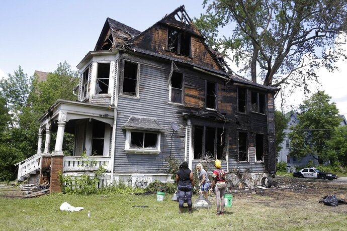 Workers clean up a duplex that was set on fire following an incident Tuesday, in Milwaukee, Wednesday, June 24, 2020. Milwaukee police say two missing teenage girls were never at the Milwaukee house that was set on fire during unrest that saw three people shot and 10 police officers and a firefighter injured as a large unruly crowd gathered at the scene of the investigation. (RIck Wood/Milwaukee Journal-Sentinel via AP)