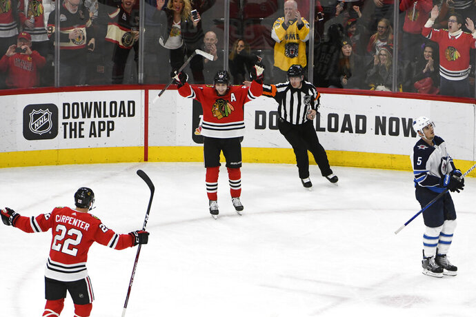 Chicago Blackhawks right wing Patrick Kane (88) celebrates his 1,0000th point on an assist against the Winnipeg Jets during the third period of an NHL hockey game Sunday, Jan. 19, 2020, in Chicago. (AP Photo/David Banks)
