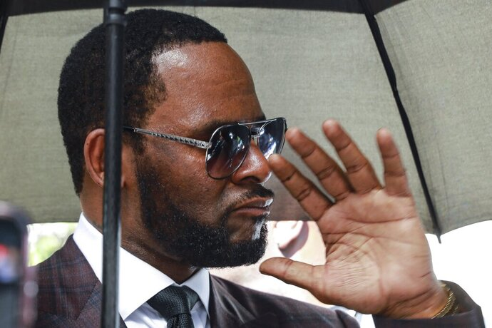 FILE - In this June 26, 2019, file photo, Musician R. Kelly departs from the Leighton Criminal Court building after a status hearing in his criminal sexual abuse trial in Chicago. elly was charged with racketeering and sex-related crimes against women and girls in sweeping New York federal indictment unsealed Friday, July 12. The 18-page indictment accuses Kelly and members of his entourage of recruiting women and girls to