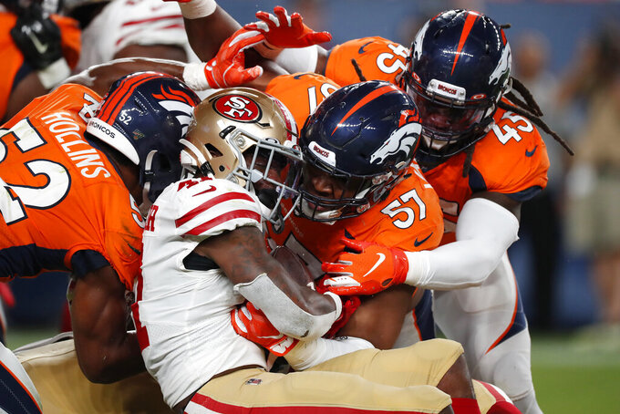 San Francisco 49ers running back Jeff Wilson Jr scores a touchdown was Denver Broncos defensive end DeMarcus Walker (57), linebacker A.J. Johnson (45) and linebacker Justin Hollins (52) defend during the second half of an NFL preseason football game, Monday, Aug. 19, 2019, in Denver. (AP Photo/David Zalubowski)