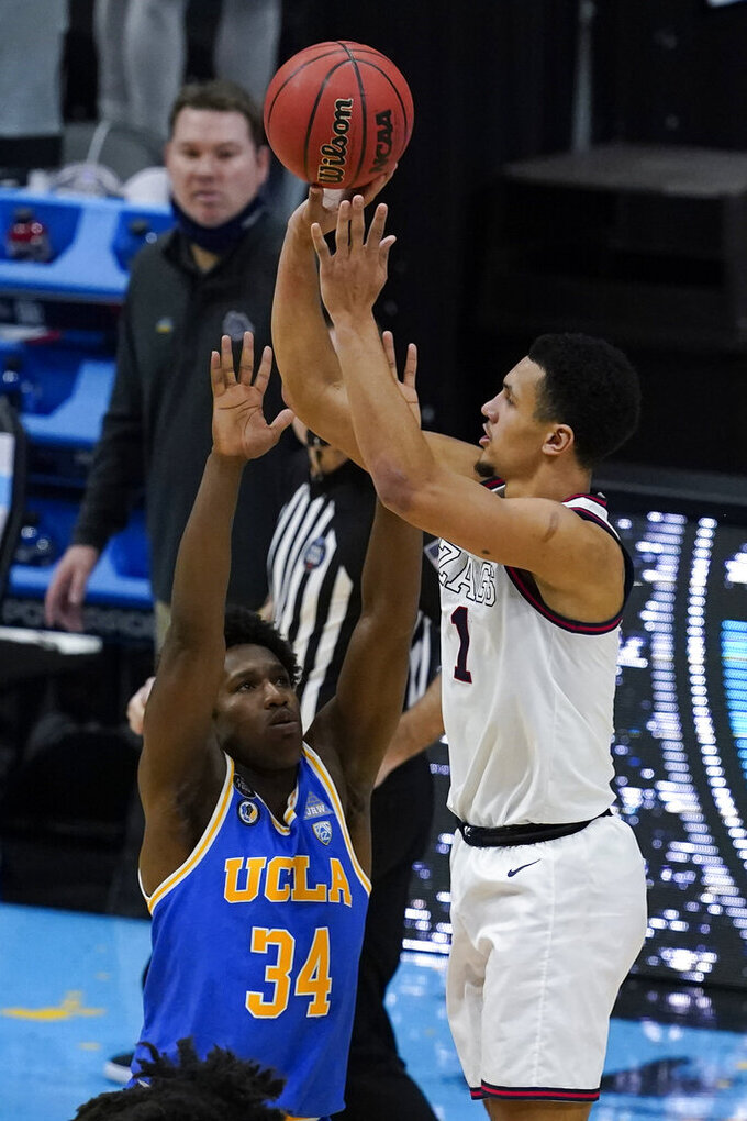 Gonzaga guard Jalen Suggs (1) shoots over UCLA guard David Singleton (34) to win the game during overtime in a men's Final Four NCAA college basketball tournament semifinal game, Saturday, April 3, 2021, at Lucas Oil Stadium in Indianapolis. Gonzaga won 93-90. (AP Photo/Darron Cummings)