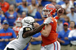 Florida quarterback Kyle Trask, right, throws a pass as he is hit by Towson linebacker Christian Dixon (55) during the first half of an NCAA college football game, Saturday, Sept. 28, 2019, in Gainesville, Fla. (AP Photo/John Raoux)