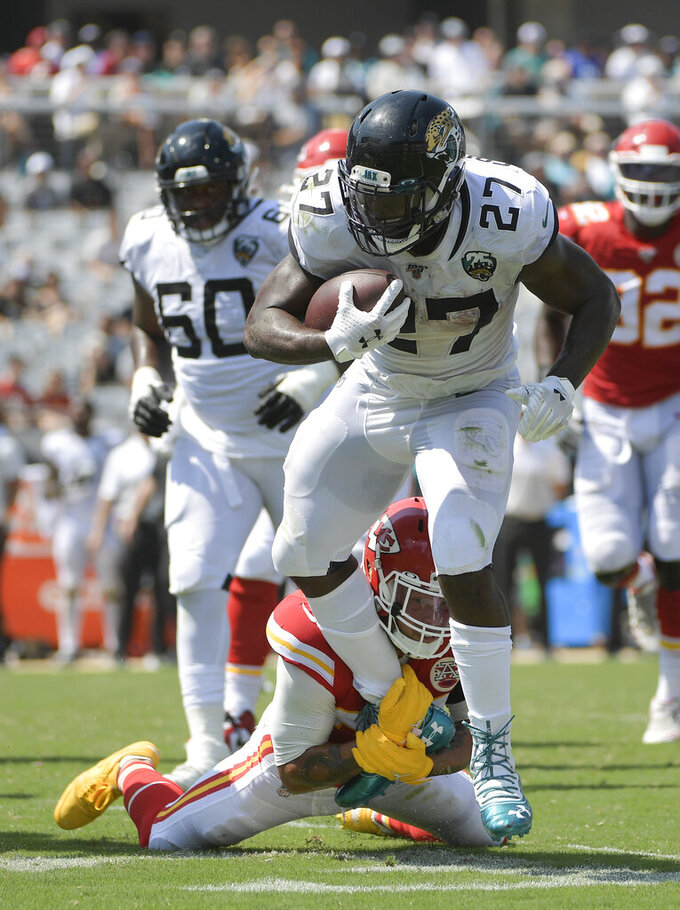 Jacksonville Jaguars running back Leonard Fournette (27) tries to avoid a tackle by Kansas City Chiefs free safety Tyrann Mathieu during the first half of an NFL football game Sunday, Sept. 8, 2019, in Jacksonville, Fla. (AP Photo/Phelan M. Ebenhack)