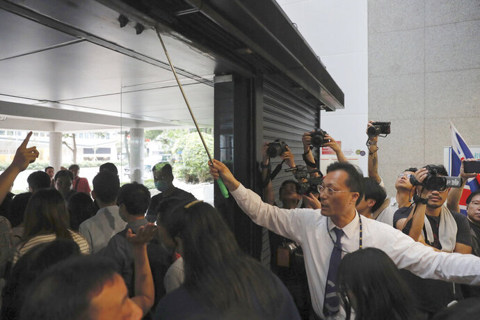 A security guard tries to close the entrance to the Hong Kong Revenue Tower as protesters block people from entering in Hong Kong on Monday, June 24, 2019. Hong Kong has been rocked by major protests for the past two weeks over legislative proposals that many view as eroding the territory's judicial independence and, more broadly, as a sign of Chinese government efforts to chip away at the city's freedoms. (AP Photo/Kin Cheung)