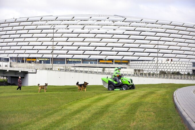 FILE - In this Wednesday, March 18, 2020 file photo, a worker rides a tractor as he mows a lawn in front of the Olympic stadium, in Baku, Azerbaijan. With coronavirus restrictions eased to allow fans back into stadiums, there at least will be some atmosphere at the tournament after months of games being played without any. Budapest wants all fans to come, while Saint Petersburg and Baku hope to use 50% of stadium capacity. (AP Photo/Aziz Karimov, File)