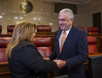 Commissioner Jenniffer Gonzalez and Senate President Thomas Rivera Schatz hold hands before a private meeting with Legislators and Mayors, in San Juan, Puerto Rico, Thursday, Aug. 8, 2019. Rivera Schatz, who played a key role in the successful court challenge to the swearing-in last Friday of Pedro Pierluisi after then-Gov. Ricardo Rossello resigned, publicly backed Gonzalez, Puerto Rico's representative to the U.S. Congress, to become governor. (AP Photo/Dennis M. Rivera Pichardo)
