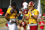 Washington Redskins quarterback Dwayne Haskins Jr. (7) and quarterback Colt McCoy (12) talk as they begin warmups during the first day of the Washington Redskins NFL football training camp in Richmond, Va., Thursday, July 25, 2019. (AP Photo/Steve Helber)
