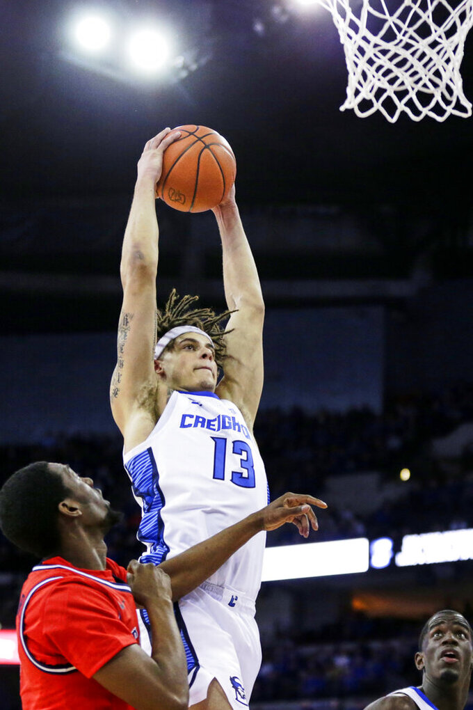 Creighton's Christian Bishop (13) goes up for a rebound against St. John's Greg Williams Jr., bottom left, during the first half of an NCAA college basketball game in Omaha, Neb., Saturday, Feb. 8, 2020. (AP Photo/Nati Harnik)