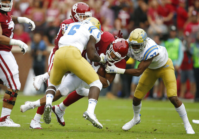 Oklahoma running back Rodney Anderson, center, is tackled by UCLA defensive back Adarius Pickett (6) and defensive back Quentin Lake (37) in the first quarter of an NCAA college football game in Norman, Okla., Saturday, Sept. 8, 2018. (AP Photo/Sue Ogrocki)