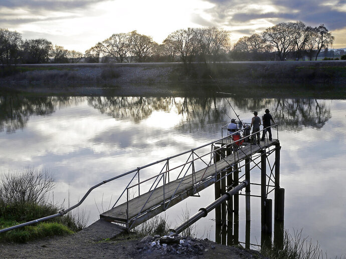 FILE - In this Feb. 23, 2016 file photo, people try to catch fish along the Sacramento River in the San Joaquin-Sacramento River Delta, near Courtland, Calif. California officials announced Thursday, Nov. 21, 2019 that they will sue the Trump administration to block its recently announced rules governing water in the San Joaquin Delta. (AP Photo/Rich Pedroncelli, File)