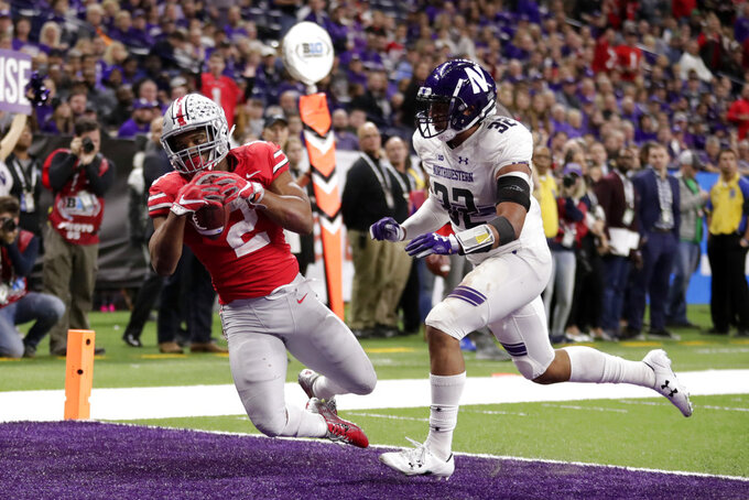 Ohio State running back J.K. Dobbins (2) catches a touchdown pass as Northwestern's Nate Hall (32) defends during the second half of the Big Ten championship NCAA college football game, Saturday, Dec. 1, 2018, in Indianapolis. Ohio State won 45-24. (AP Photo/Michael Conroy)