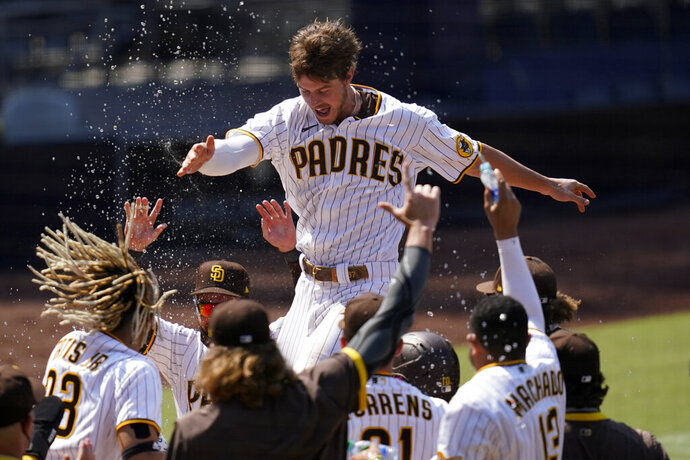 FILE - In this Aug. 27, 2020 file photo, San Diego Padres' Wil Myers, top, reacts after hitting a three-run walkoff home run to defeat the Seattle Mariners in a baseball game in San Diego. Wil Myers is back. While Manny Machado and Fernando Tatis Jr. have grabbed most of the attention on the playoff-bound Padres, Myers' comeback performance has also been instrumental in returning San Diego to postseason play for the first time since 2006. Myers is hitting .291 with 14 homers and 38 RBIs in 52 games. (AP Photo/Gregory Bull, File)