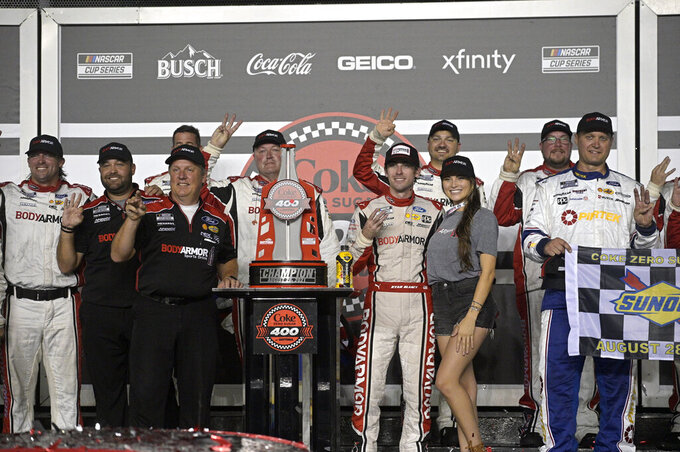 Ryan Blaney, standing to the right of the champion trophy, poses with his girlfriend Gianna Tulio and crew members in Victory Lane after winning a NASCAR Cup Series auto race at Daytona International Speedway, Saturday, Aug. 28, 2021, in Daytona Beach, Fla. (AP Photo/Phelan M. Ebenhack)