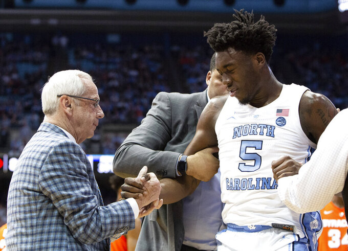 North Carolina coach Roy Williams, left, helps North Carolina's Nassir Little (5) off the floor after he was inadvertently hit in the eye during the second half of the team's NCAA college basketball game against Syracuse in Chapel Hill, N.C., Tuesday, Feb. 26, 2019. (AP Photo/Ben McKeown)