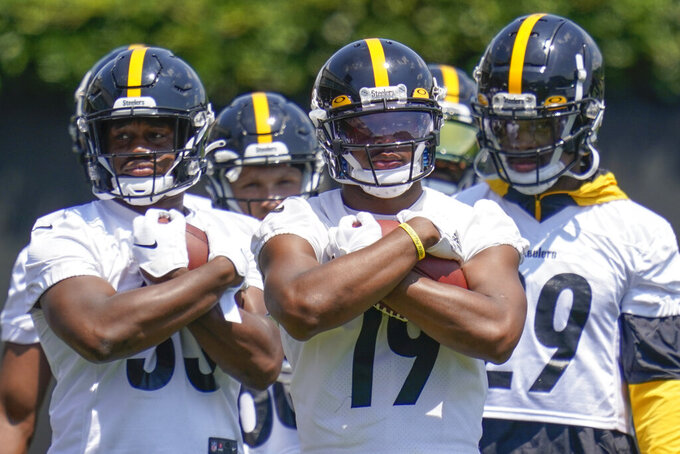 Pittsburgh Steelers wide receiver JuJu Smith-Schuster (19) center, holds a ball with teammates during a drill at an NFL football practice, Thursday, July 22, 2021, in Pittsburgh. (AP Photo/Keith Srakocic)