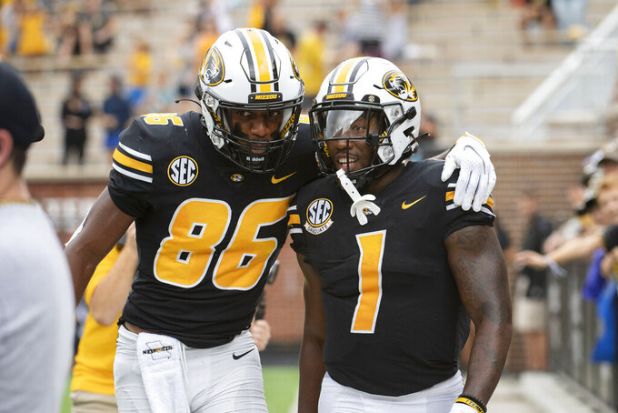 Missouri running back Tyler Badie, right, celebrates with teammate Tauskie Dove, left, after scoring a touchdown during the first half of an NCAA college football game against Central Michigan, Saturday, Sept. 4, 2021, in Columbia, Mo. (AP Photo/L.G. Patterson)