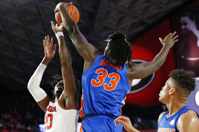 Florida center Jason Jitoboh (33) blocks a shot from Georgia's Rayshaun Hammonds (20) during the first half of an NCAA college basketball game Wednesday, March 4, 2020, in Athens, Ga. (Joshua L. Jones/Athens Banner-Herald via AP)
