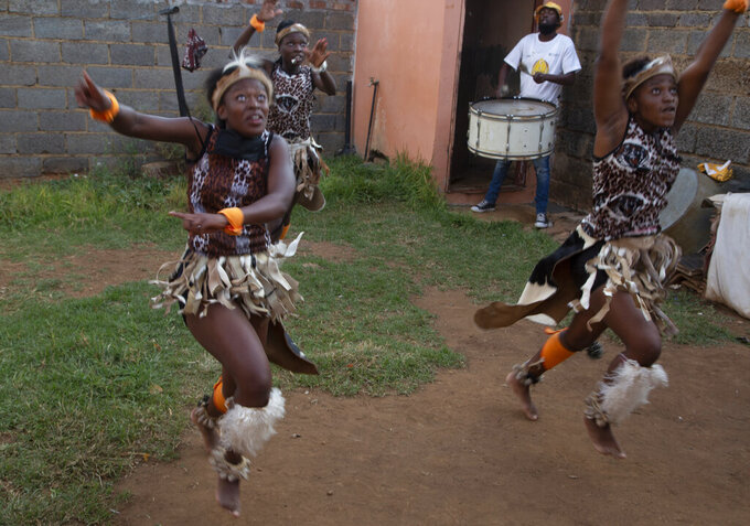 A group of girls perform traditional Zulu dance in the yard of a home in the Orange Farm Township south of Johannesburg, Wednesday, April 14, 2021.  Amid the classes in dancing and marimba music, a leader of the culture group praised Britain's Prince Philip, who died last week and whose Duke of Edinburgh Awards helped to fund the culture group's activities. (AP Photo/Denis Farrell)