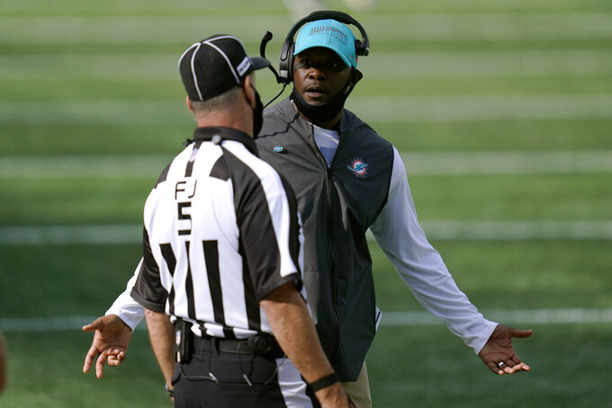 Miami Dolphins head coach Brian Flores, right, appeals to field judge Jim Quirk in the second half of an NFL football game against the New England Patriots, Sunday, Sept. 13, 2020, in Foxborough, Mass. (AP Photo/Charles Krupa)