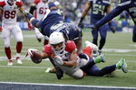 Arizona Cardinals wide receiver Larry Fitzgerald (11) scores a touchdown as Seattle Seahawks defensive tackle Quinton Jefferson dives for the tackle during the first half of an NFL football game, Sunday, Dec. 22, 2019, in Seattle. (AP Photo/Elaine Thompson)