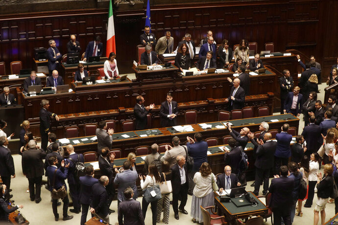 Italian Premier Giuseppe Conte, background center, acknowledges the applause at the end of a confidence vote at the Lower Chamber in Rome, Monday, Sept. 9, 2019. Conte is pitching for support in Parliament for his new left-leaning coalition ahead of crucial confidence votes. (AP Photo/Gregorio Borgia)
