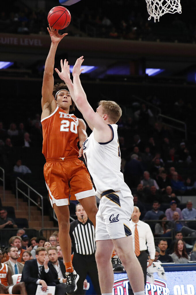 Texas forward Jericho Sims (20) passes around California forward Lars Thiemann (21) during the second half of an NCAA college basketball game in the 2K Empire Classic, Thursday, Nov. 21, 2019, in New York. (AP Photo/Kathy Willens)