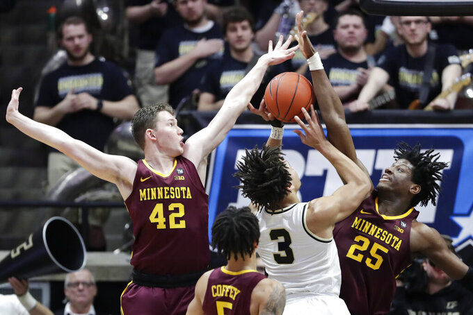 Purdue guard Carsen Edwards (3) ties to shoot between Minnesota forward Michael Hurt (42) and center Daniel Oturu (25) during the first half of an NCAA college basketball game in West Lafayette, Ind., Sunday, Feb. 3, 2019. (AP Photo/Michael Conroy)