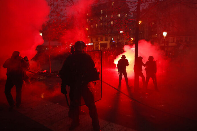 Riot police officers secure an area during a demonstration in Paris, Thursday, Dec. 5, 2019. Small groups of protesters are smashing store windows, setting fires and hurling flares in eastern Paris amid mass strikes over the government's retirement reform. (AP Photo/Thibault Camus)