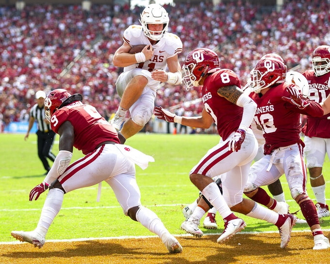 FILE - In this Oct. 6, 2018, file photo, Texas quarterback Sam Ehlinger (11) leaps into the end zone to score against Texas during an NCAA college football game at the Cotton Bowl in Dallas. The Texas-Oklahoma rivalry is never short on bad blood between the Big 12 border states. (Nick Wagner/Austin American-Statesman via AP, File)
