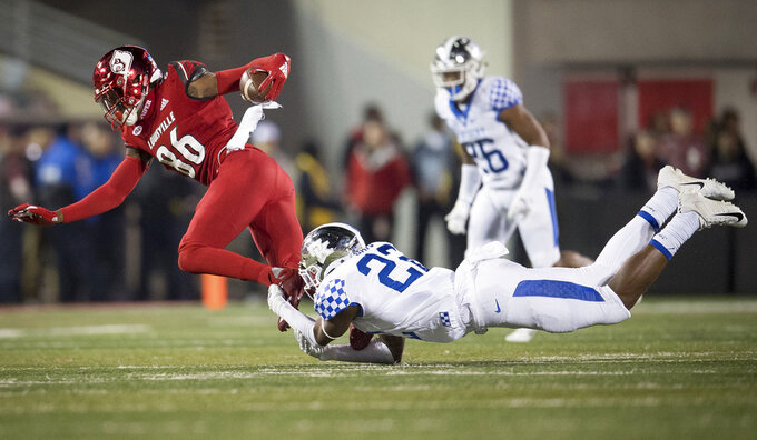 Louisville wide receiver Devante Peete (86) is tackled by Kentucky safety Tyrell Ajian (23) during the second half of the NCAA college football game in Louisville, Ky., Saturday, Nov. 24, 2018. (AP Photo/Bryan Woolston)