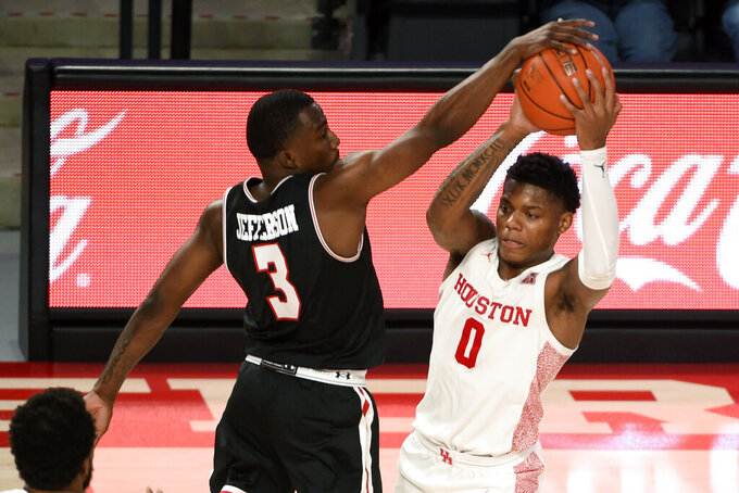 Houston guard Marcus Sasser (0) looks to pass as Lamar guard Ellis Jefferson (3) defends during the second half of an NCAA college basketball game, Wednesday, Nov. 25, 2020, in Houston. (AP Photo/Eric Christian Smith)