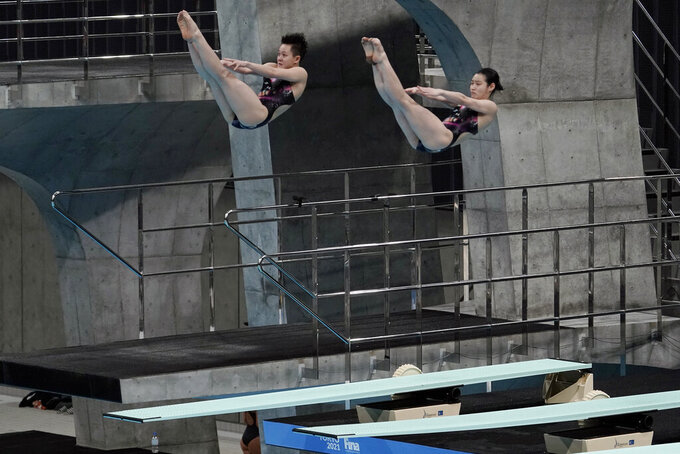 Chang Yani and Chen Yiwen of China dive during the women's synchronized 3-meter springboard preliminary at the FINA Diving World Cup Saturday, May 1, 2021, at the Tokyo Aquatics Centre in Tokyo. (AP Photo/Eugene Hoshiko)