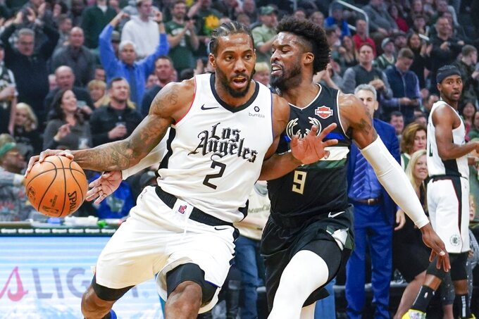 LA Clippers' Kawhi Leonard drives past Milwaukee Bucks' Wesley Matthews during the first half of an NBA basketball game Friday, Dec. 6, 2019, in Milwaukee. (AP Photo/Morry Gash)