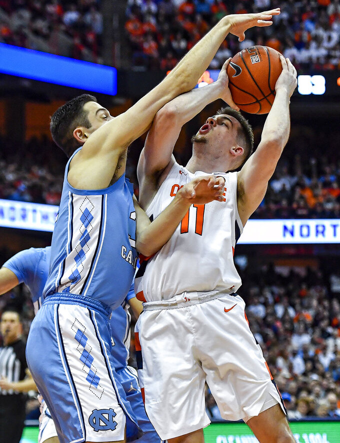 Syracuse guard Joseph Girard III, right, is defended by North Carolina forward Justin Pierce during the second half of an NCAA college basketball game in Syracuse, N.Y., Saturday, Feb. 29, 2020. North Carolina defeated Syracuse 92-79. (AP Photo/Adrian Kraus)