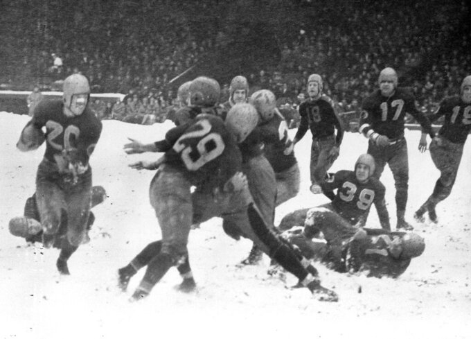 FILE - In this Nov. 21, 1937, file photo, Washington Redskins' Cliff Battles, left, carries the ball against the Cleveland Rams in the third quarter of a football game at Cleveland Stadium. (AP Photo/Cleveland Plain Dealer)/The Plain Dealer via AP)