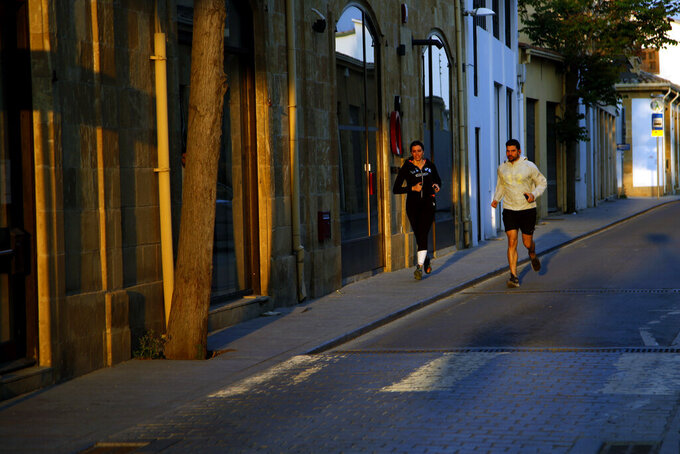 A couple jog in a street past closed shops, during the lockdown measures by government to prevent the spread of coronavirus pandemic in the medieval core in central capital Nicosia, Cyprus, on Wednesday, April 29, 2020. Cyprus' president Nicos Anastasiades announcements from May 4 the island starts to ease its lockdown restrictions from coronavirus pandemic. (AP Photo/Petros Karadjias)