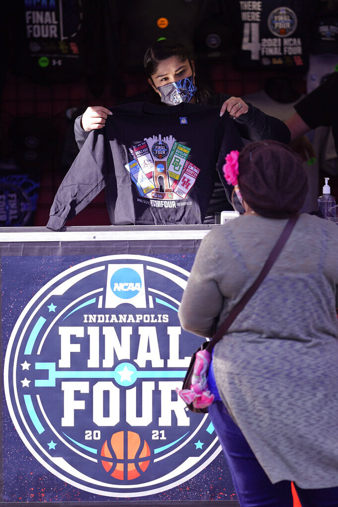 A vendor shows off a t-shirt before a college basketball game during the Final Four round of the NCAA tournament at Lucas Oil Stadium in Indianapolis, Saturday, April 3, 2021. (AP Photo/AJ Mast)