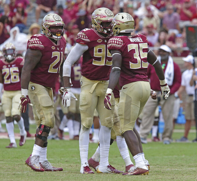 FILE - In this Oct. 20, 2018, file photo, Florida State's Brian Burns, center, celebrates sacking Wake Forest's quarterback with teammates Marvin Wilson, left, and Leonard Warner during an NCAA college football game, in Tallahassee, Fla. Burns has nine sacks on the season and 7½ in the last three games. According to Pro Football Focus, Burns leads the nation in quarterback pressures with 46 on the season.(AP Photo/Steve Cannon, File)