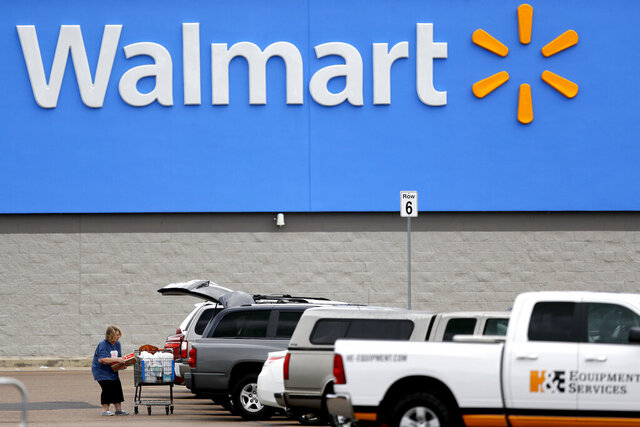 FILE - In this March 31, 2020 file photo, a woman pulls groceries from a cart to her vehicle outside of a Walmart store in Pearl, Miss. Walmart will require customers to wear face coverings at all of its namesake and Sam's Club stores. The company said the policy will go into effect on Monday, July 20, 2020 to allow time to inform stores and customers. (AP Photo/Julio Cortez, File)