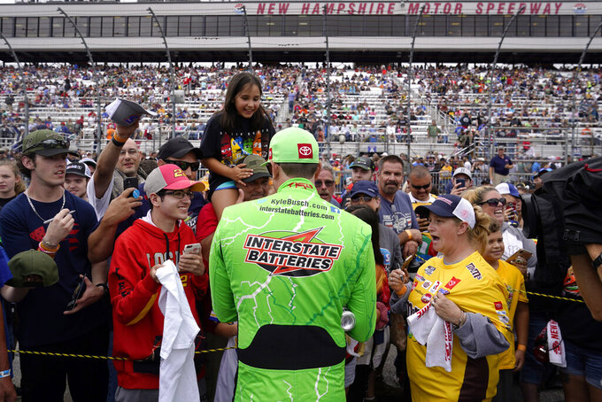 Kyle Busch signs autographs for fans prior to the NASCAR Cup Series auto race Sunday, July 18, 2021, in Loudon, N.H. (AP Photo/Charles Krupa)