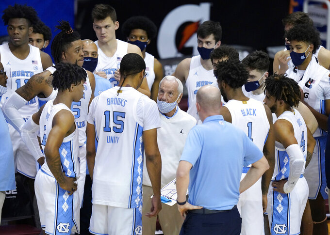 North Carolina head coach Roy Williams talks with his team just before the end of an NCAA college basketball game for the championship of the Maui Invitational, Wednesday, Dec. 2, 2020, in Asheville, N.C. Texas won 69-67. (AP Photo/Kathy Kmonicek)
