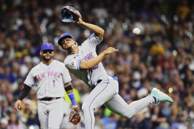 New York Mets' Francisco Lindor, right, is unable to throw Milwaukee Brewers' Eduardo Escobar out at first base during the sixth inning of a baseball game Saturday, Sept. 25, 2021, in Milwaukee. (AP Photo/Aaron Gash)