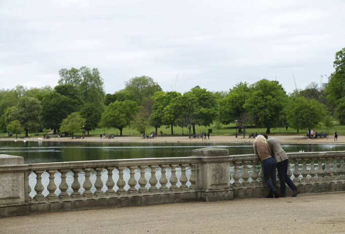 People in a sparsely populated Hyde Park, with the Serpentine lake, in central London, as the UK continues in lockdown to help curb the spread of the coronavirus, Sunday May 3, 2020.  The highly contagious COVID-19 coronavirus has impacted on nations around the globe, many imposing self isolation and exercising social distancing when people move from their homes. (Yui Mok / PA via AP)